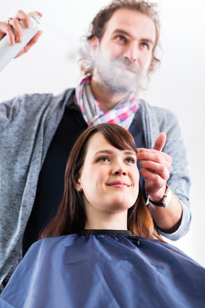 coiffeur: Male coiffeur giving women hairstyling with hairspray in shop