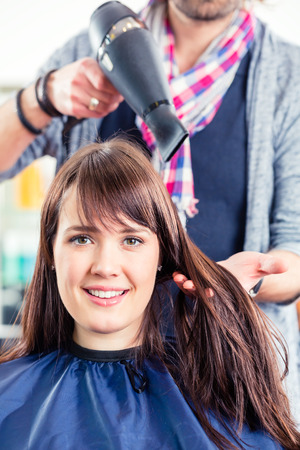 Hairdresser blow dry woman hair in shop photo