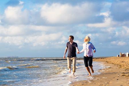 Couple enjoying romantic sunset at north sea beach photo