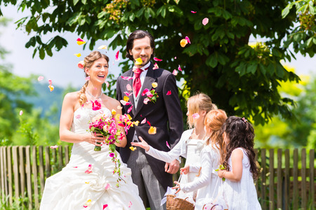 Wedding couple bride and groom with flower children or bridesmaid in white dress and flower baskets photo