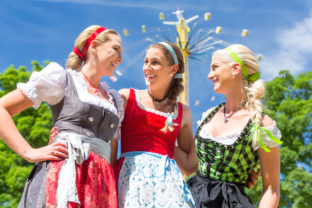 chairoplane: Women friends visiting Bavarian folk festival in  Dirndl standing in front of carousel  Stock Photo