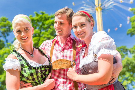 Women friends visiting Bavarian folk festival in  Dirndl standing in front of carousel  Stock Photo