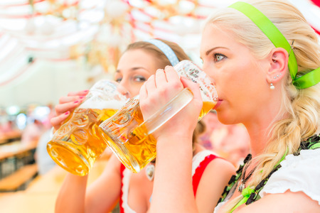 Women drinking Bavarian beer in tent on Oktoberfest or dult wearing dirndl photo