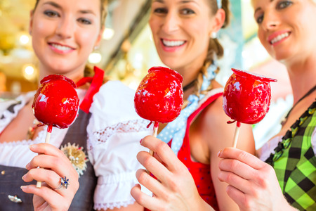 candy apple: Friends visiting together Bavarian fair in national costume eating candy apple
