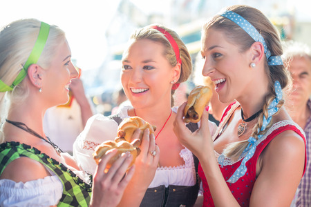 Friends visiting together Bavarian fair in national costume eating grilles sausage in bread roll Stock Photo