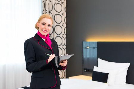 Housekeeping manager of assistent controlerende hotelkamer of pak met checklist op netheid