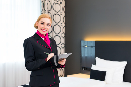 Housekeeping manager or assistant controlling hotel room or suit with checklist on tidiness Stok Fotoğraf - 31529822