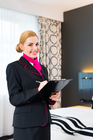 Housekeeping manager or assistant controlling hotel room or suit with checklist on tidiness  photo