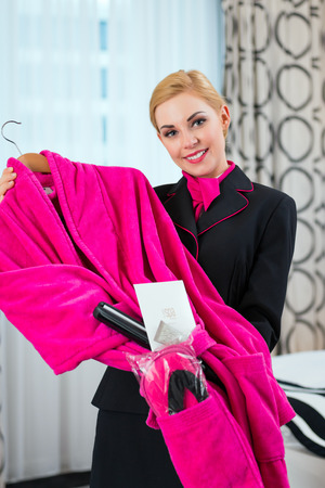 Housekeeping manager taking care of bathrobe in hotel room  photo