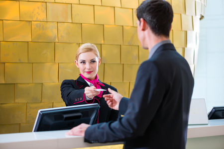 to check: Man in Hotel check in at reception or front office being given key card Stock Photo