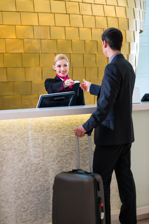 Man in Hotel check in at reception or front office being given key card photo