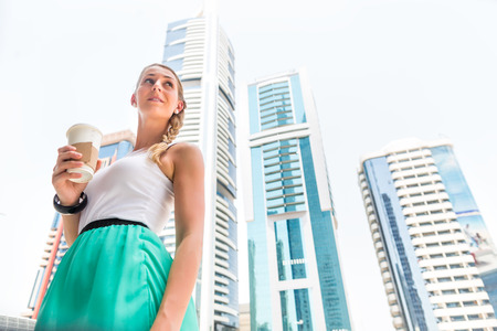 metropolitan: Young woman drinking coffee in metropolitan city Dubai