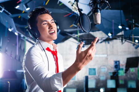 micro recording: Asian professional musician recording new song or album CD in studio