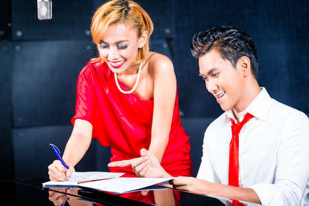 composing: Asian professional singer and pianist working and discussing on new song in studio for composing and recording Stock Photo