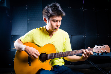 asian produce: Asian professional guitarist playing acoustic guitar music in recording studio