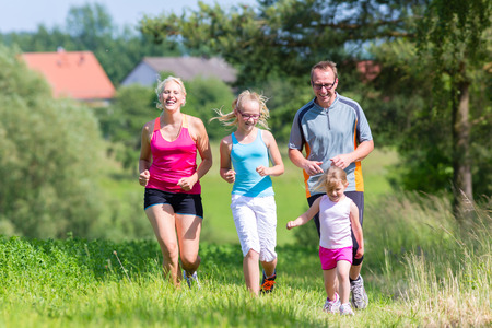 Parents with two children sport running outdoors photo