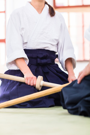 Man and woman fighting with wooden swords at Aikido training in martial arts school  photo
