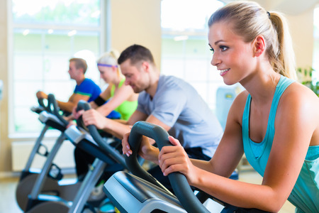 Group of fitness people in sport gym spinning on bicycles Stock Photo
