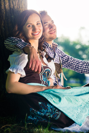 tracht: Bavarian couple in Tracht hugging under tree
