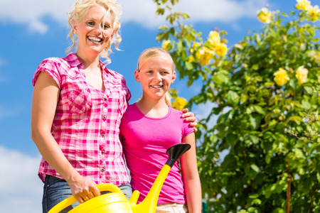 Mother and daughter working in garden watering plants with can in front of rose bushes photo