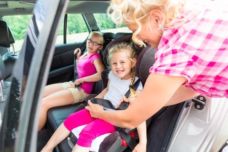 asiento coche: Madre abrocharse el cinturón de niño en el asiento de seguridad para automóvil