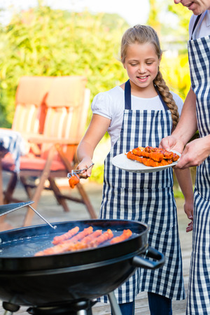 Family of Father and daughter barbecue meat spits at family garden BBQ  photo