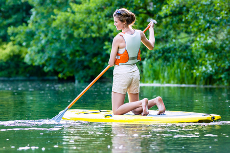 sup: Woman paddling with surfboard sup on forest river