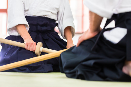Man and woman fighting with wooden swords at Aikido training in martial arts school Фото со стока - 31530122