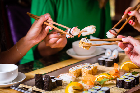 Young people eating sushi in Asian restaurant Stok Fotoğraf