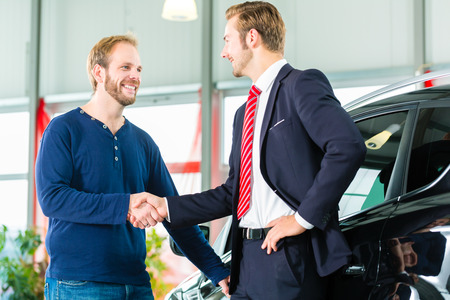 Seller or car salesman and customer in dealership, they shaking hands and seal the purchase of the auto or new car