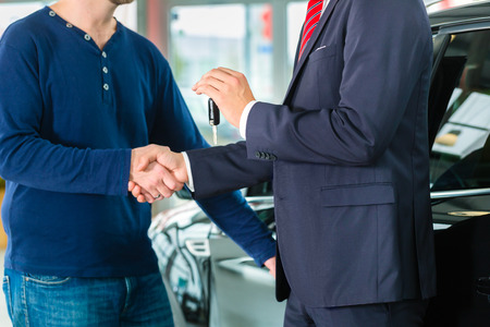 Seller or car salesman and customer in auto dealership, they shaking hands, hands over the car keys and seal the purchase of the auto or new car Stok Fotoğraf - 32044004
