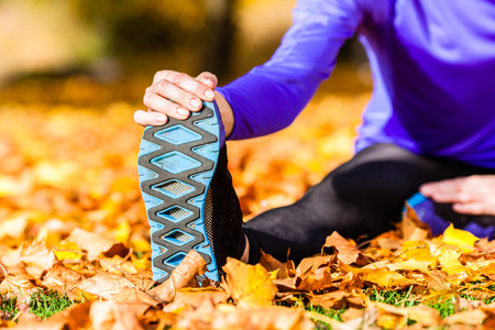 Sportswoman sport stretching in autumn leaves photo