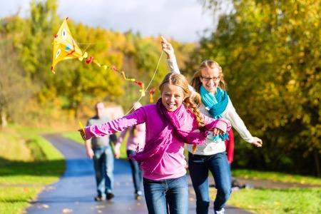 Familie zu nehmen Spaziergang im Herbstwald fliegenden Drachen