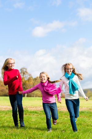 Girls having fun running through fall or autumn park  photo