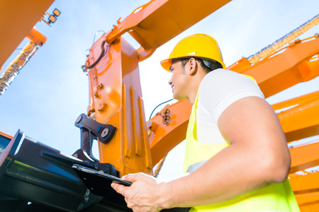 Asian worker controlling construction machinery of building site or mining company photo
