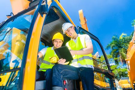 maquinaria pesada: Conductor de maquinaria de construcción de Asia discutir con planos capataz en el cojín o tableta computadora de obra Foto de archivo