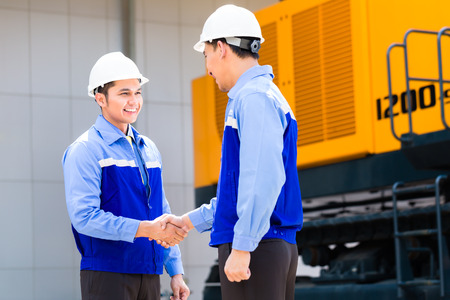 Asian engineer having agreement handshake at construction machinery of construction site or mining company 写真素材