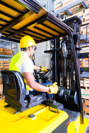 Asian fork lift truck driver lifting pallet in storage warehouse photo