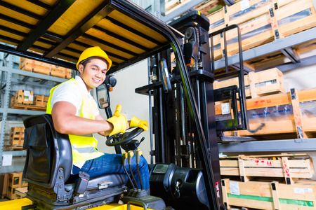 warehouse equipment: Asian fork lift truck driver lifting pallet in storage warehouse
