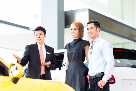Asian couple buying car in auto dealership consulting the salesman  Archivio Fotografico