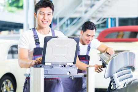 garage automobile: Asie mécanique automobile chinois de contrôle automatique du moteur avec l'outil de diagnostic dans son atelier