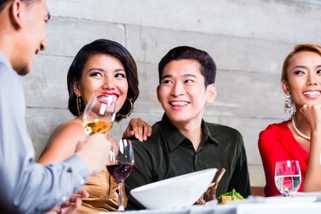 asian men: Asian friends, two couples, dining in fancy restaurant eating good food and drinking wine