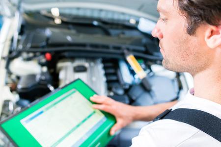 garage automobile: M�canicien avec outil de diagnostic en atelier de voiture Banque d'images