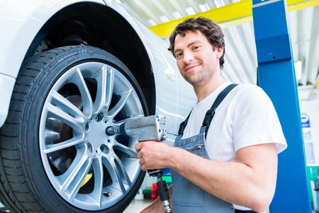 summer tire: Male mechanic changing car tire or tyre in workshop Stock Photo