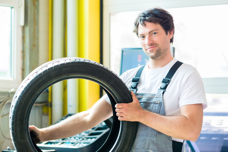 changing seasons: Auto mechanic changing tire in car workshop