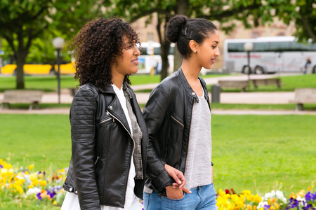 Two north African teen friends take a walk in the park talking  photo