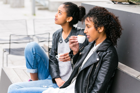 Two north African teen friends drinking together coffee outside  photo