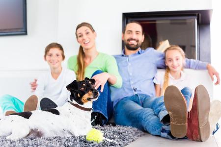 mujer con perro: Familia que se sienta junto con el perro en el piso de la sala de estar en la chimenea
