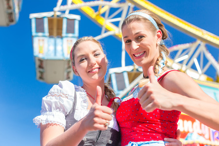 Friends visiting together Bavarian fair in national costume or Dirndl in front of ferris wheel photo
