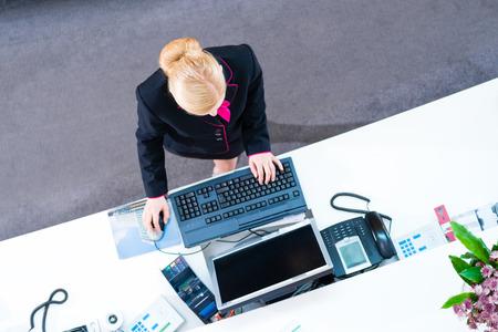 Hotel receptionist working on computer at front desk office  Standard-Bild